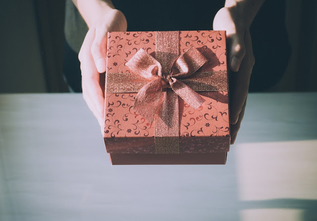 Person holding out a mocha-colored gift box with a mocha-colored ribbon