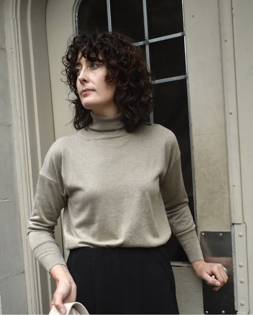 Woman with short curly hair wearing the Evam Eva Turtleneck