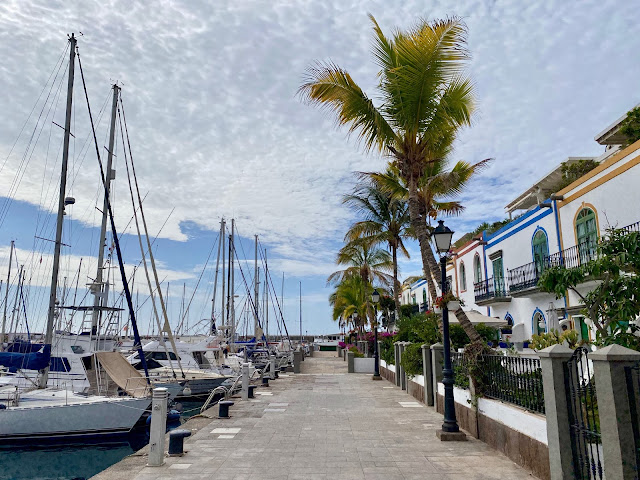 White houses with colourful gardens next to boats in the harbour at Puerto Mogan, Gran Canaria, Spain