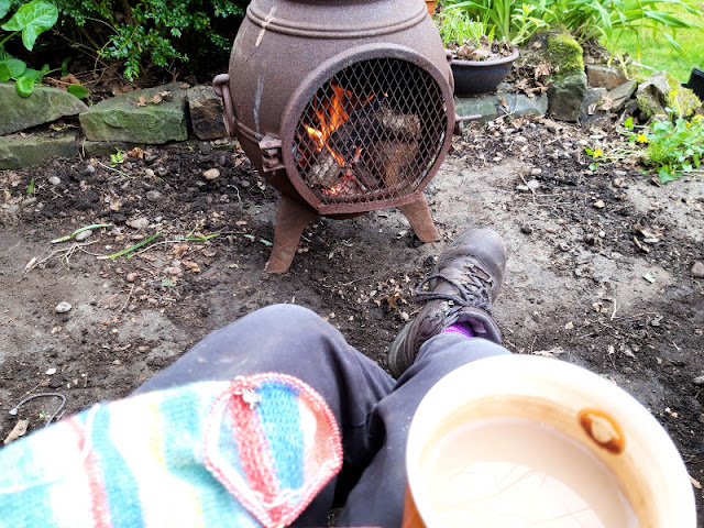 Image shows a person sitting in front of a burning chiminea.  On the left knee is a striped sock, and on the right knee is a mug of tea