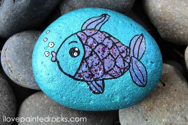 Rainbow Fish inspired fish painted rock with glitter scales