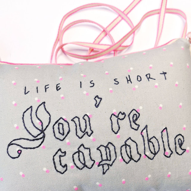 close up of Life is short You're Capable embroidery and thin ribbon shown in the background