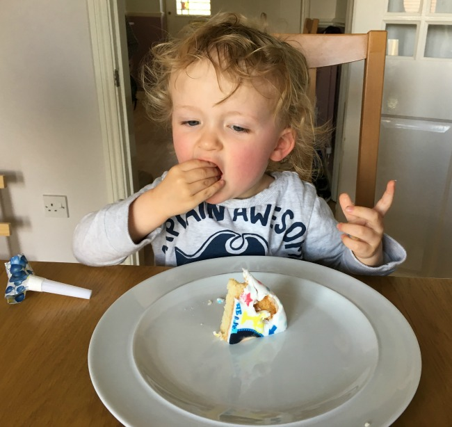 toddler putting cake in mouth