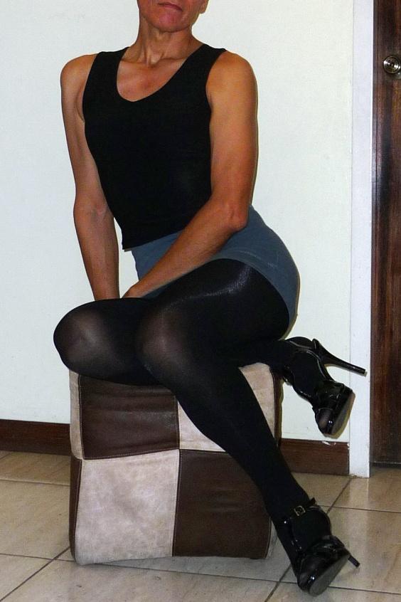 Feminine girl wearing gray mini skirt, black tights and black high heeled sandals