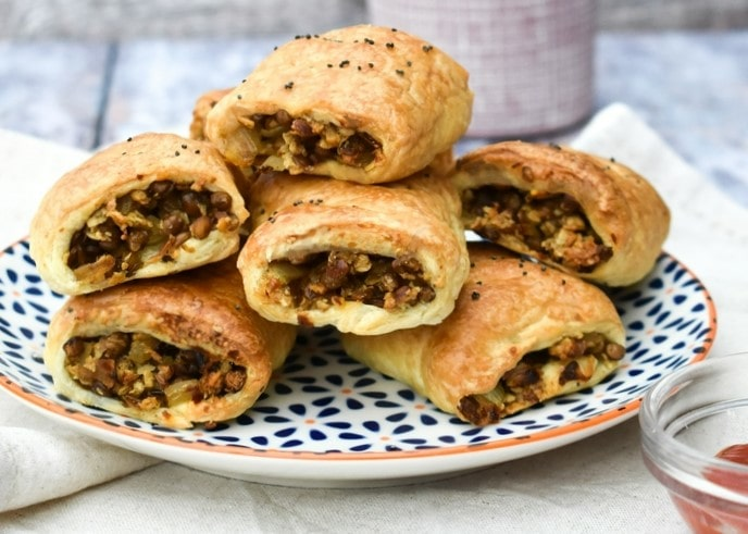 Mini lentil sausage rolls stacked on a plate