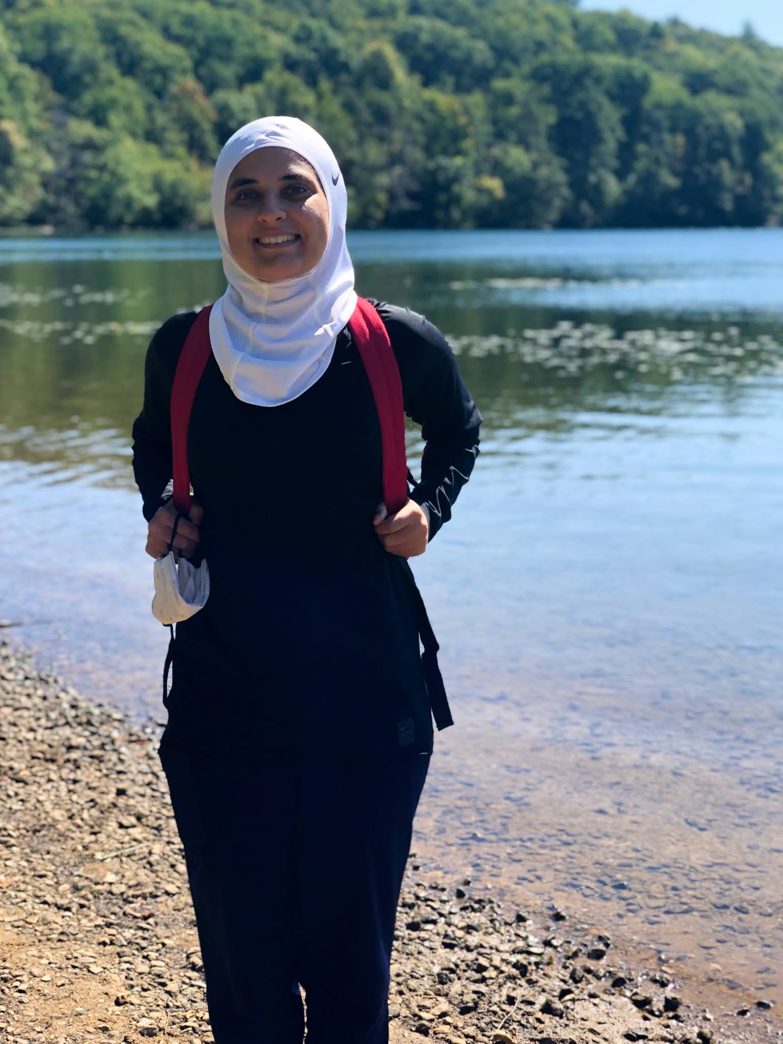 Sahara at lake, nike white scarf, nike black shirt, blue joggers - smiling at camera.