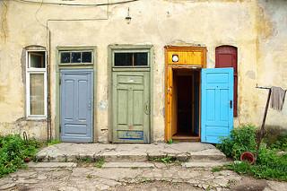Puertas de colores, dos cerradas, una abierta.