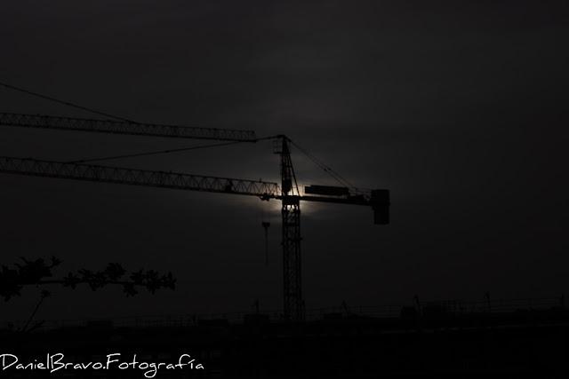 Fotografía de una grúa de obra a contraluz. La grúa está muy oscura y se ve el Sol por detrás de la grúa