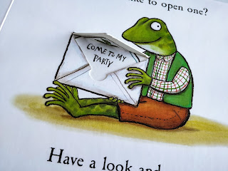 "An up close photo of a frog wearing brown trousers, a  shirt with green and red check lines under a green vest jacket is holding an open letter that reads ""come to my party""."