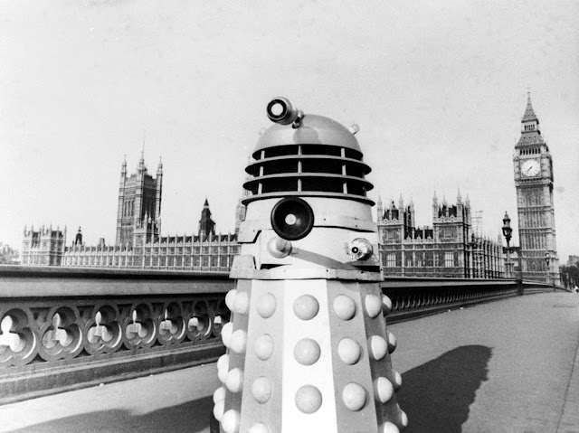 A Dalek on Westminster Bridge, aiming its gun-stick at us, the Houses of Parliament behind