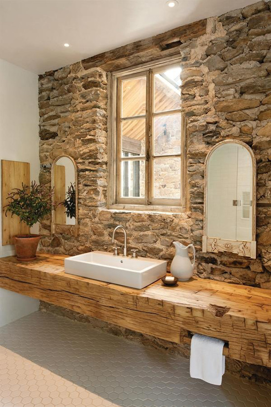 Bare stone wall bathroom. Photo by Lara Swimmer via Custom Homes.