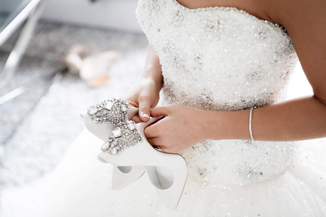 Image of bride wearing wedding dress and holding a pair of shoes on her wedding day.
