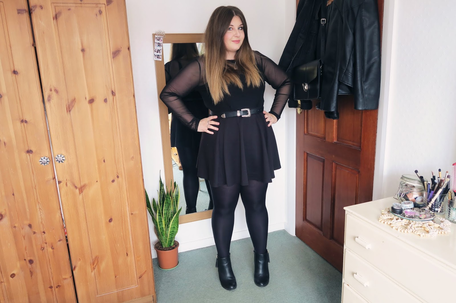 Wearing a black skater skirt, a black mesh top, and black heeled boots