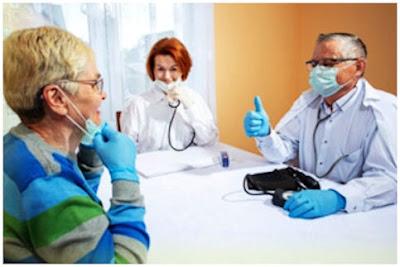 Pöydän äärellä potilas, sairaanhoitaja ja lääkäri, joka kohottaa peukkua!