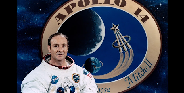 Apollo astronaut Edgar Mitchell in front of a graphic of the mission patch. Credits: NASA