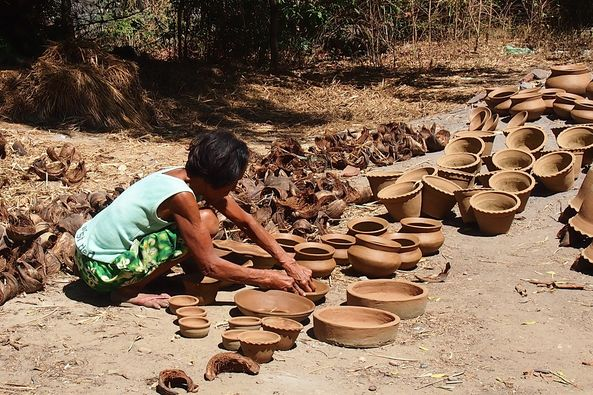 woman drying red clay pots under the sun