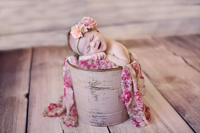 newborn baby girl in a bucket smiling, Orange County newborn photographer