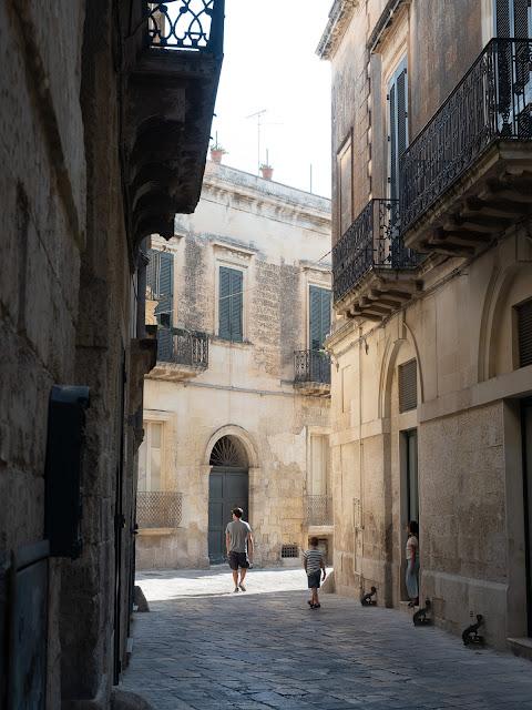 Hombre y dos niños en una calle barroca en Lecce