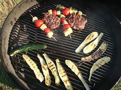 Verschiedenes Gemüse und Fleisch auf Grill. Zucchini, Auberginen, Burger, Spieße mit Tomate.