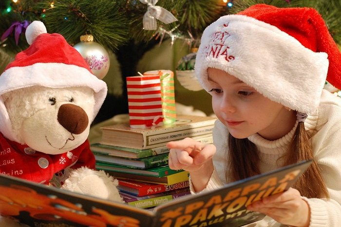 girl reading christmas books in front of tree