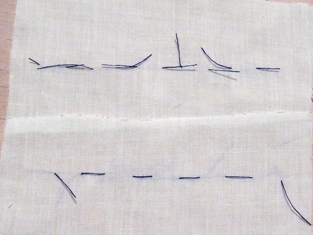 Punto flojo cortado con hilo azul sobre tela blanca