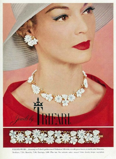 Model Jean Patchett wearing red dress and hat in ad for Trifari Jewelry 1956