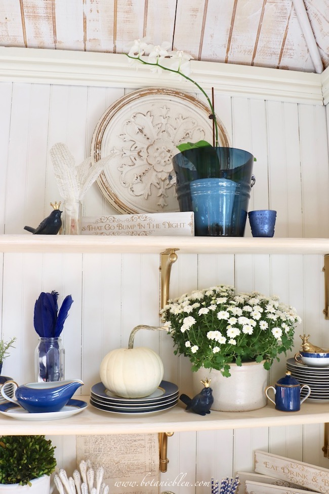 White pumpkins and chrysanthemums celebrate fall on open shelves with gold brackets