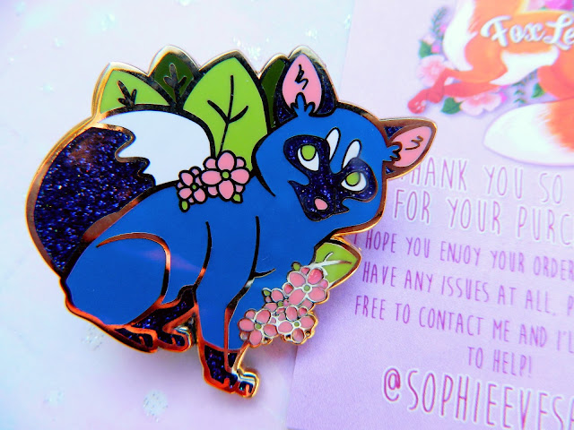 A photo of beautiful blue fox enamel pin with flowers and leaves, by FoxLeap!
