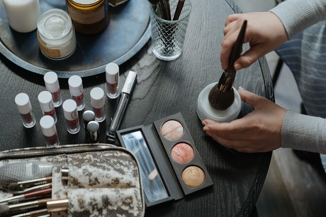 The image shows a selection of make-up and skincare laying out on a dresser table. There is a woman using a make-up brush to apply some powdered product to her face