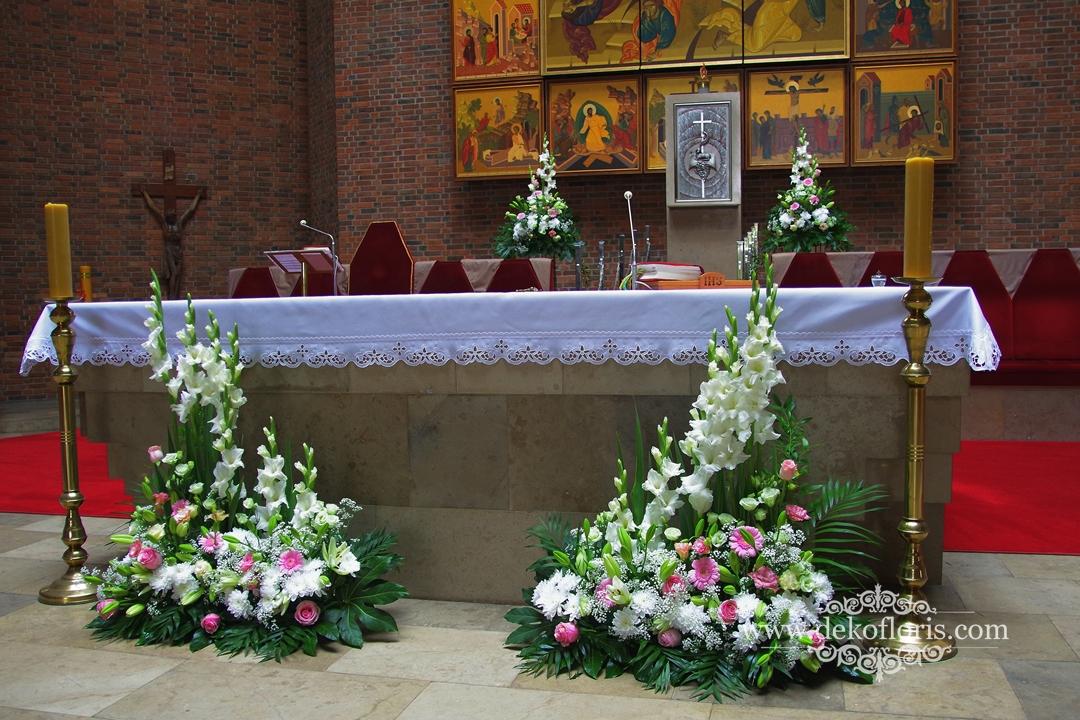 Kompozycje różowych kwiatów przed ołtarzem