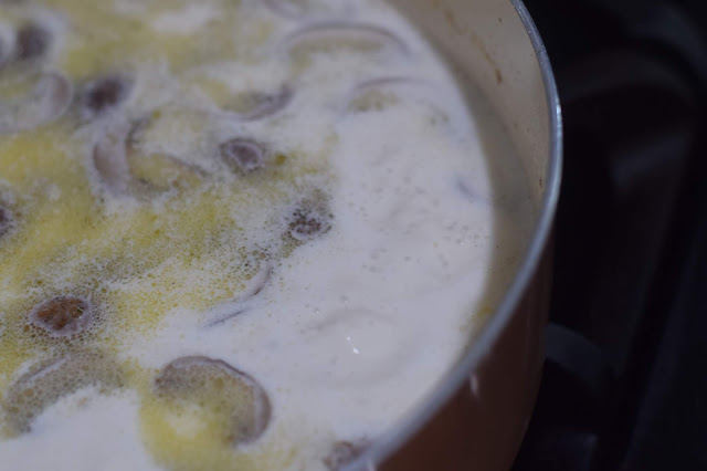 The chicken broth and heavy cream coming to a boil in the pan on the stove.