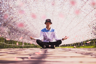 """A man sits cross-legged, arms out in a stereotypical """"meditation"""" post, on a stone path under a hemicylindrical trellis over which pink flowers or leaves have been trained."""