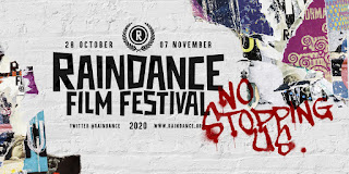 "Raindance Film Festival written on a white brick wall surrounded by torn film posters and a graffiti'd ""No Stopping Us"""