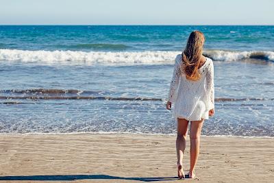 Chica paseando por la playa con un vestido