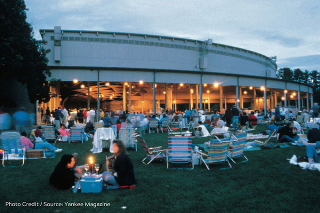 picnickers on the grass outside a lit open-air auditorium