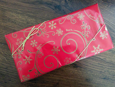 A box of See's Candy wrapped in red Christmas wrapping.