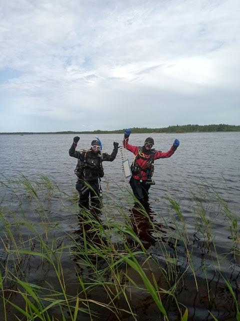 Kaksi sukelluspukuista työntekijää kädet ilmassa seisovat rantavedessä.