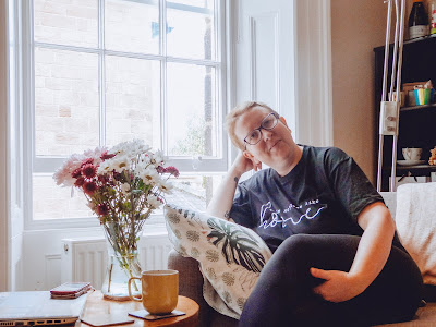 Sarah sitting on her couch wearing a black t shirt which says 'There's No Place Like Home'
