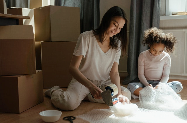 a mom and a daughter packing their possessions in storage boxes
