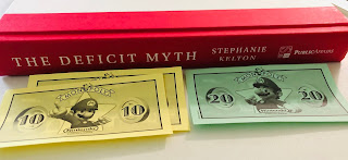 The Deficit Myth with yellow and green monopoly money