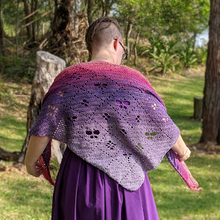 Sarah is standing with back to the camera looking down, her arms are raised slightly as she rearranges her shawl. It is crochet cotton yarn in a gradient from pale purple to dark purple to pink. It has filet design of a grid with motifs of flowers, butterflies and dragonflies. She is standing in a grassy clearing surrounded by trees.