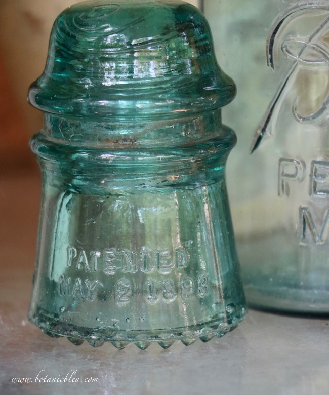 Antique electrical insulators and canning jars are stored on an outdoor table