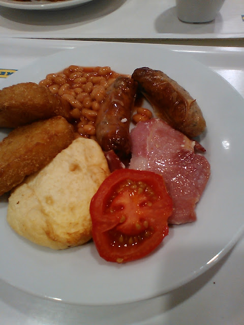 An ikea breakfast, sausage, egg, tomato, hash browns, bacon and beans