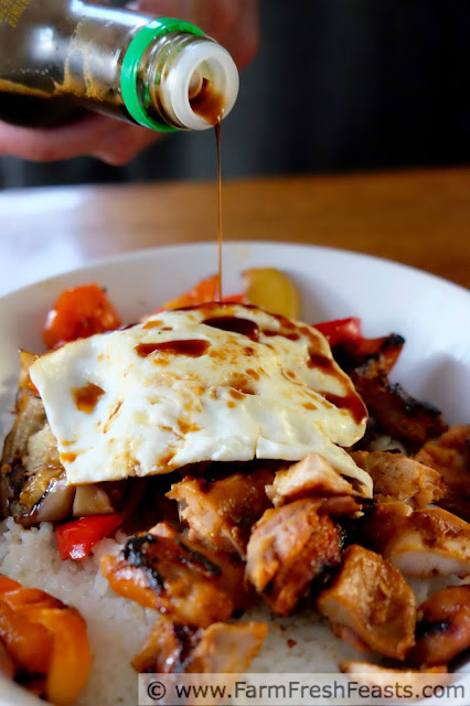 a close up of soy sauce being poured atop a fried egg with Korean-seasoned grilled chicken, eggplant, and peppers in a rice bowl