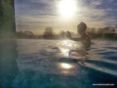 Mental Health is really important. Take time out when you need to. Image is a photograph of a young woman in an infinity pool with trees in the background and a setting Autumn sun