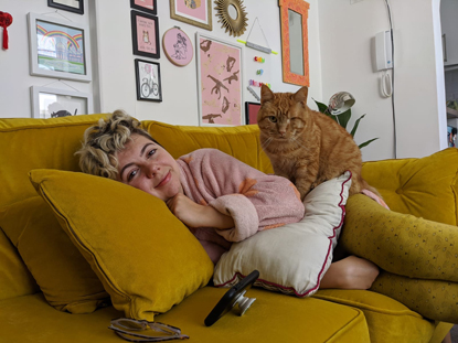 Woman lying on yellow sofa with ginger cat sitting on her