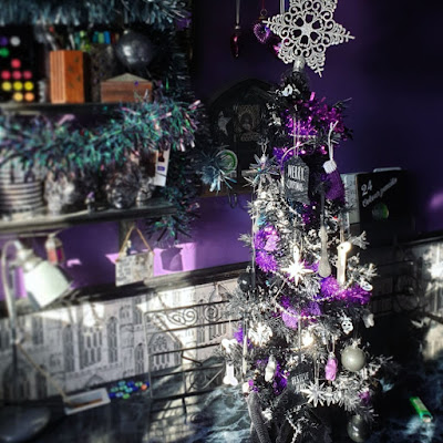 A photograph of Christmas decorations. The wall behind is purple, there is a black dado rail, and greyscale wallpaper of Gothic arches. There are three shelves on the right holding art materials, and the upper two shelves are garlanded with tinsel, grey at the top, iridescent green and purple in the middle. There is a 2 and a half foot tall black Christmas tree densely decorated, with a glittery snowflake on the top that is too large and leans slightly to the right. The tree is on a desk with a fake black marble work-surface. The bottom of the tree is wrapped in a Hallowe'en table-cloth of black lace. The tree is decorated in a purple and silver colour-scheme, with skulls and stars as the primary motifs; it has lots of tinsel. Behind the tree is an ornate black metal stand for a tablet computer.  There is a grey vintage-style desk-lamp on the desk.