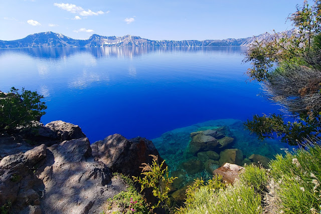Beautiful crystal blue lake with lush brush in the foreground and mountainous edge of the lake on the horizon