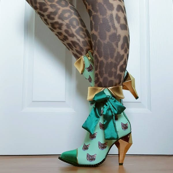 wearing green cat ankle boots with gold cuff and large satin bow on side