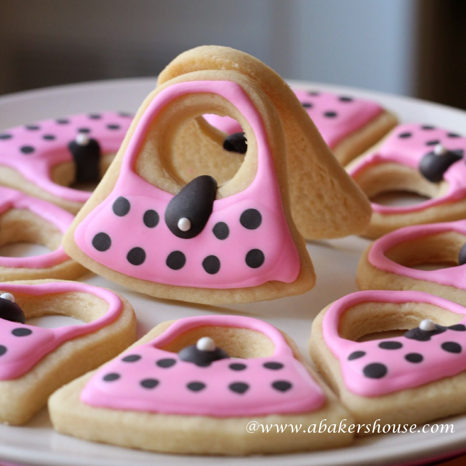 plate of decorated sugar cookies topped with pink and black royal icing in the shape of purses